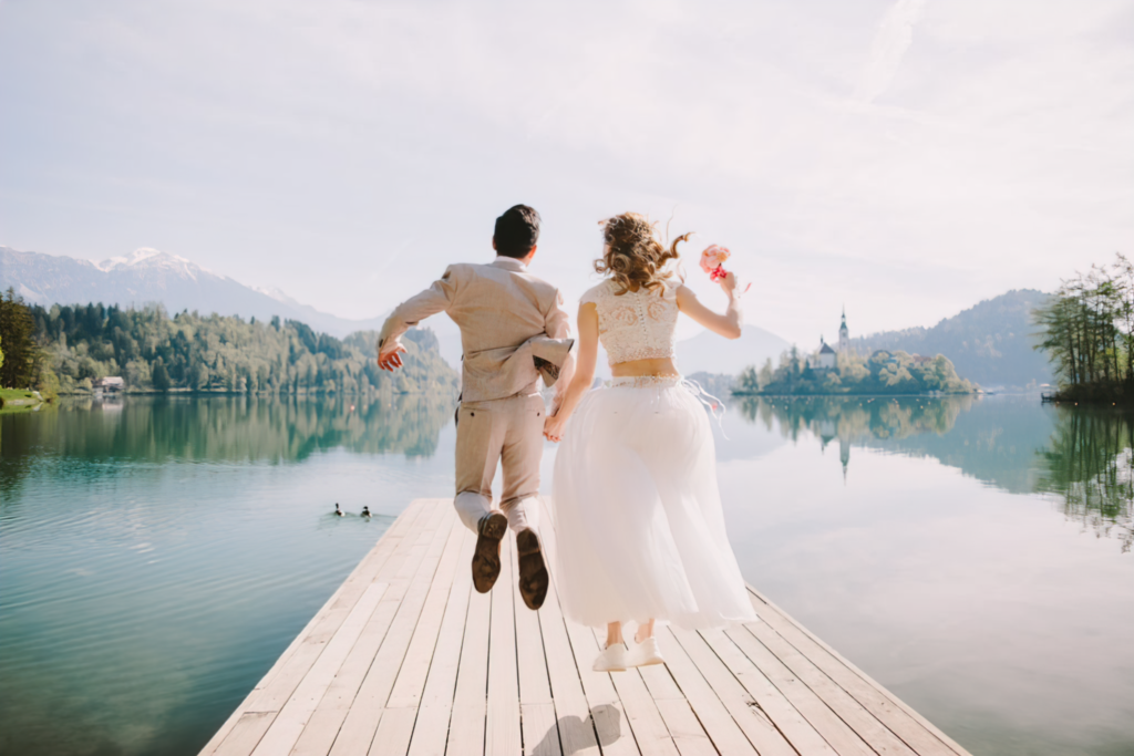 Bride Groom Jumping On River Jetty