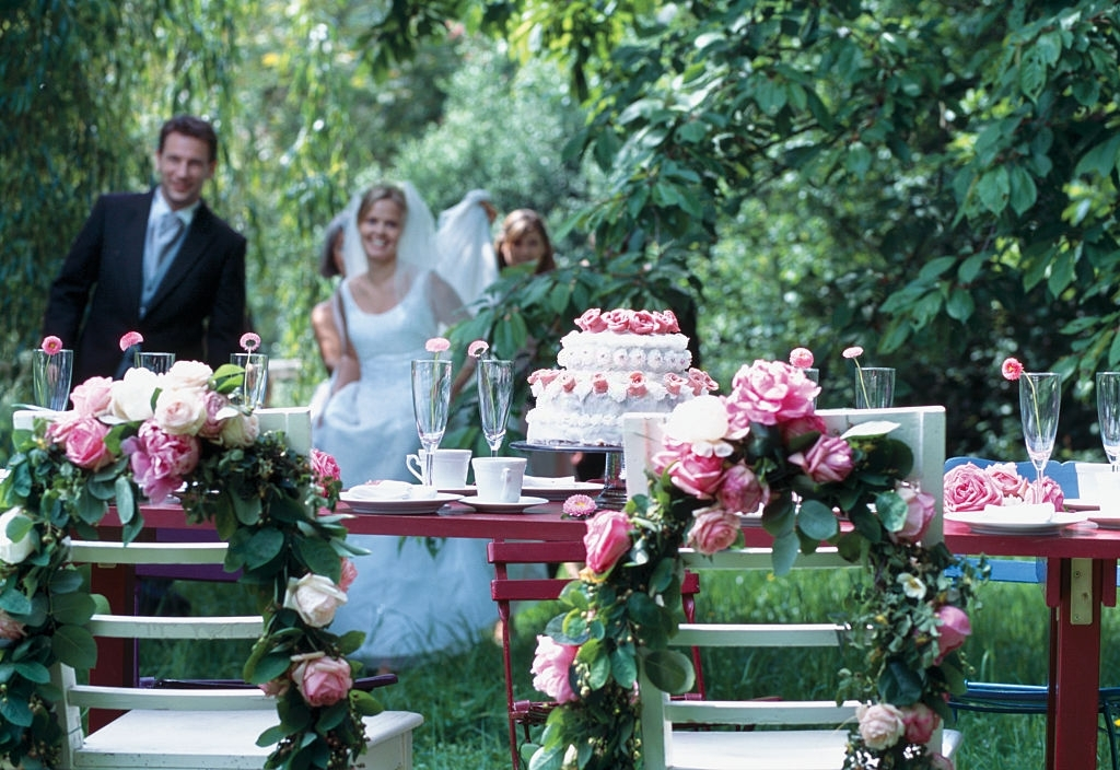 Happy Couple With Their Wedding Cake In The Garden